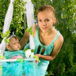 Stock Photo: Mom shakes her baby on a swing on nature