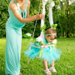 Mother and baby on a swing on nature — Stock Photo