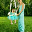 My mother shakes her baby on a swing — Stock Photo #31397855