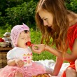 Stock Photo: Picnic, mother feeds child strawberries