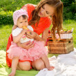 图库照片: Picnic, mother feeds her baby