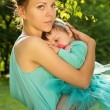 Stock Photo: Protection mother hugs baby