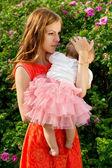 çiçekler bir arka plan üzerinde bir bebek tutan mutlu anne — Stok fotoğraf