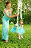 Anne ve bebek doğa bir salıncak üzerinde — Stok fotoğraf