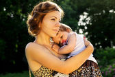 Mãe abraçando bebê na sunset — Fotografia Stock