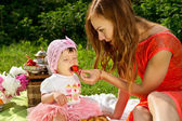 Picnic, mother feeds the child strawberries — Stock Photo