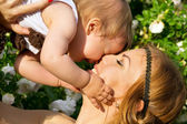 Mutlu anne ve zemin çiçek çocuk portresi — Stok fotoğraf
