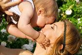 Retrato de la feliz madre y el niño sobre un fondo de flores — Foto de Stock