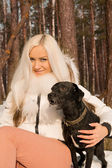 A young girl with a dog in the forest — Stock Photo