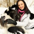 Girl plays with a dog in the woods in winter — ストック写真