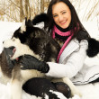 Girl plays with a dog in the woods in winter — Stockfoto
