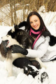 Girl plays with a dog in the woods in winter — Stock Photo