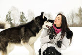 Young girl with a dog in winter — Stock Photo