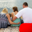 Family sitting by the sea — Stock Photo #39889739