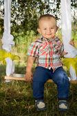 A little boy sits on a swing — Stock Photo
