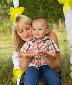 Happy mother's ride on a swing with son — Stock Photo
