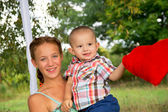 Happy sister's ride on a swing with brother on the nature.jpg — Stock Photo