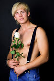 Muscular beautiful guy with a rose in his hand — Stock Photo
