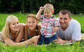 Parents with children lay on the grass — Stock Photo