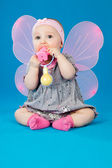 Baby with wings and toy — Stock Photo