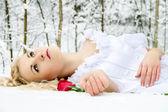 Chica en bosque de invierno con una rosa — Foto de Stock