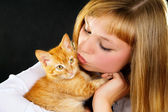 Beautiful girl holding a kitten on the hands — Stock Photo