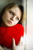 Beautiful girl longing for her beloved and keeps the heart — Stock Photo