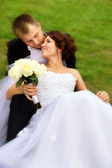 Beautiful newlyweds lay on the grass — Stock Photo