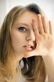 Happy girl covers her hand eye — Stock Photo