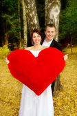 Newlyweds holding a heart — Foto Stock