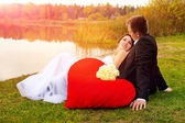Newlyweds sitting on the grass — Stock Photo