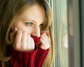 Sad girl looking out the window waiting for her husband — Stock Photo