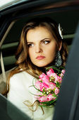 Beautiful bride sitting in the car — Stock Photo