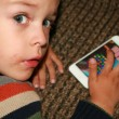 Toddler playing game on screen phone — Stock Photo
