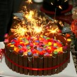 Birthday cake with smarties and sparklers — Stock Photo