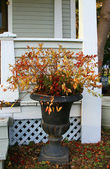 Black urn decorated with fall branches and berries — Stock Photo