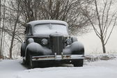 Vintage classic car covered in winter snow — Stock Photo