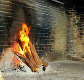 Burning logs in a brick fireplace — 图库照片