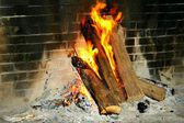 Burning logs in a brick fireplace — Stockfoto