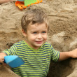 Small boy in a dug out sand hole — Stock Photo #50272695