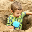 Small boy in a dug out sand hole — Stock Photo #50272699
