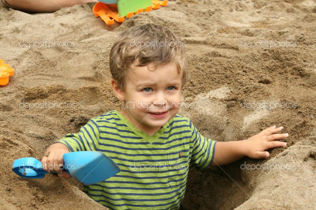 Ni o peque o en un cavado hoyo arena foto de stock - Foto nino pequeno ...