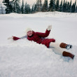 Stock Photo: Girl lying in snowbank in winter day.