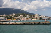 Pier with fishermen on a background of mountains and the city of Yalta, Crimea, Ukraine — Stock Photo