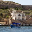 A small motor boat with tourists on the background of modern buildings and walls of the Genoese fortress of the XIV century, Balaklava, Crimea, Ukraine — Stock Photo
