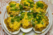 Eggs stuffed with beef liver and egg yolks and decorated with fresh chopped chives on a plate closeup — Stockfoto