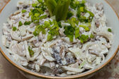 Salad of squid with mushrooms, garnished with chopped green onion closeup — Stock Photo