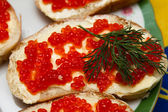 Sandwiches with red caviar adorned with leaves dill — Stock Photo