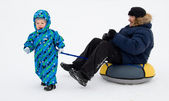 A child carries on dad tubing (inflatable sled) — Stock Photo
