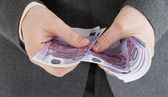 Stack banknotes of 500 euro in male hands — Stock Photo